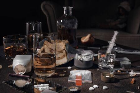 Varias drogas, alcohol y cigarrillos están sobre la mesa de madera. Sustancias que causan dependencia a las drogas y al alcohol. Clave baja.
