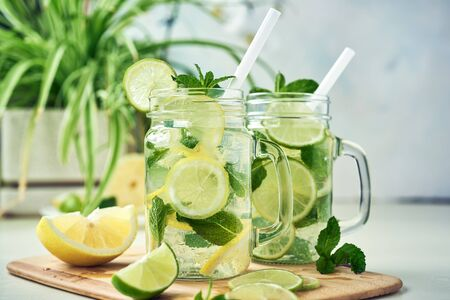 Two glasses of homemade lemon, lime, and mint lemonade sit on the wooden dining table. Cold, refreshing summer lemonade or mojito.