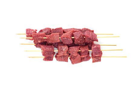 Pieces of fresh meat on bamboo skewers on a white background. Fresh meat skewers on skewers. The view from the top.