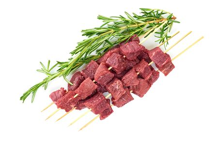 Pieces of fresh meat on bamboo skewers and a branch of rosemary on a white background. Fresh meat skewers on skewers and a branch of rosemary. The view from the top.