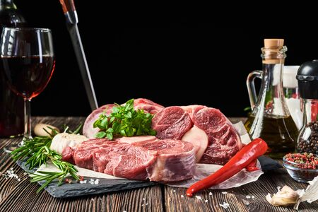 Three chunks of beef steaks from the shin, lying on a stone Board on an old wooden table. In the background, various seasonings and spices, vegetables and herbs, a glass of wine. Free space for text.