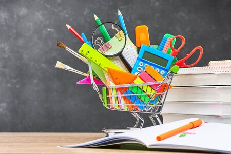 Various office supplies for school in a cart, textbooks and an open notebook, on a wooden table against a blackboard. The concept of preparing for school, the beginning of a new school year.