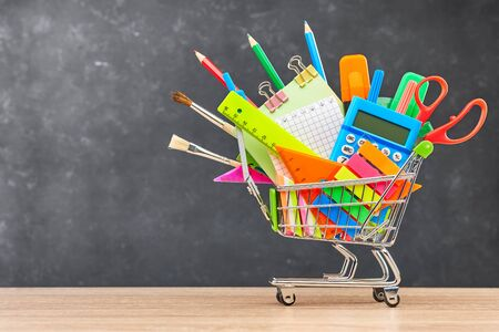 Various office supplies for school in a cart on a wooden table on a blackboard background. The concept of preparing for school, the beginning of a new school year.