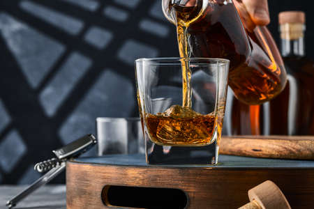 Square glass of whiskey with ice on a tray, the glass is filled with whiskey from the bottle. Square glass of brandy on a tray on a blue background, the glass is filled with brandy from a bottle.