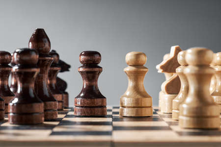 Wooden chess pieces on a chessboard, opposing pawns of different colors, the concept of strategy, planning and decision-making. The concept of leadership and teamwork to achieve success.