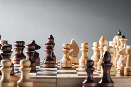 Wooden chess pieces on a chessboard, opposing pawns of different colors, the concept of strategy, planning and decision-making. The concept of leadership and teamwork to achieve success. Banque d'images