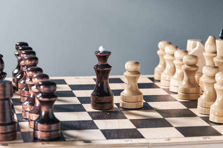 Wooden chess pieces on a chessboard, the confrontation of the white pawn and the black queen, planning and decision-making concept. The concept of leadership and teamwork to achieve success.