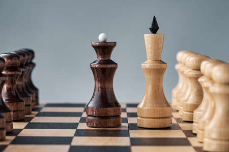 Wooden chess pieces on a chessboard, the confrontation of the white king and the black queen, the concept of planning and decision-making. The concept of leadership and teamwork to achieve success.