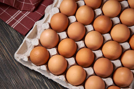 Brown chicken eggs lie in a cardboard egg tray, close-up, organic protein of natural origin, free space for text. Rustic natural products.