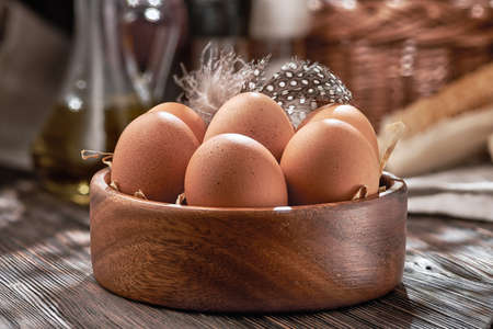Brown chicken eggs close-up in a wooden bowl, organic protein of natural origin, free space for text. Rustic natural products. Archivio Fotografico