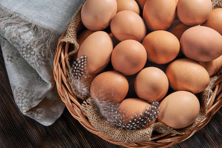 Brown chicken eggs close-up in a wicker wooden basket, organic protein of natural origin, free space for text. Rustic natural products. Archivio Fotografico