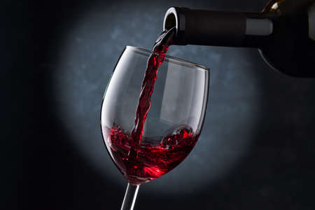 Red wine is poured into a glass from a bottle on a blurry blue background, a stream of red wine from the bottle swirls in the glass, close-up. Free space for text.
