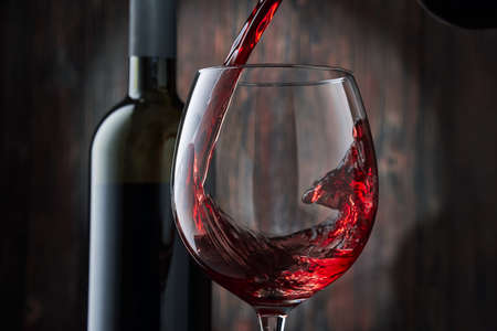 Red wine is poured into a glass from a bottle on a blurred wooden background, a stream of red wine from the bottle swirls in the glass, close-up. Free space for text.
