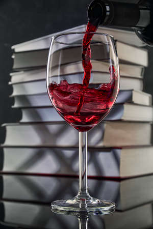 Red wine is poured into a glass from a bottle against the background of a stack of books, a stream of red wine from the bottle swirls in the glass, close-up. Free space for text.