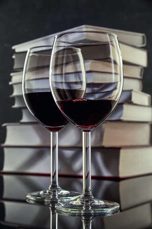 Two glasses of red wine against a stack of books, close-up. Free space for text.