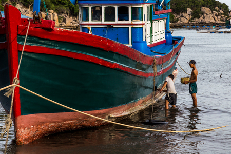 Two fisherman painting a fishing boat in a harbour