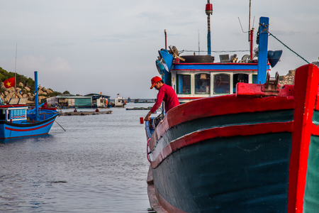 Vietnamese fishing boats being painted whilst at anchor Editorial