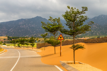 An empty raod in vietnam with sand built up on it and mountains in the background Stock Photo