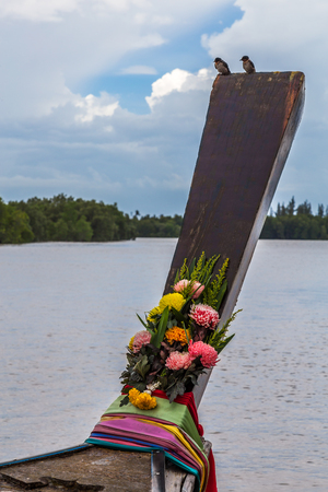 A longtail boat with two small birds and some flowers in a river Stock Photo