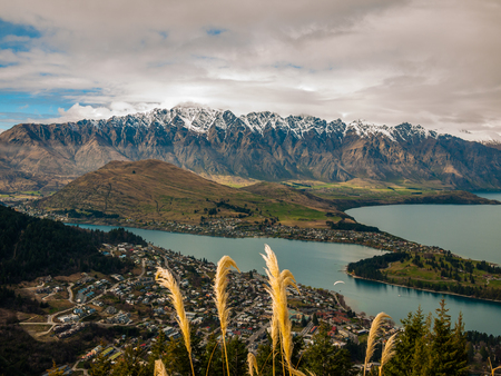 Cloudy sky snowy mountains and a town by a lake