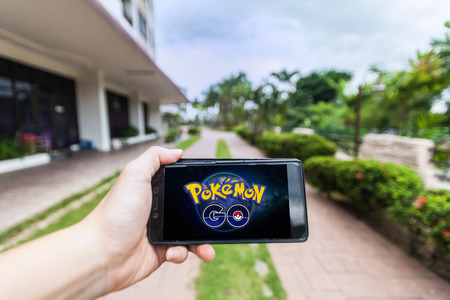 California, United States, 16 July 2016 : Hand holding a cellphone to play Pokemon Go with blur walking path background Editorial