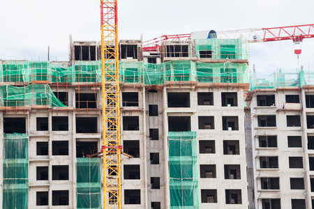 house under construction: Construction site view of crane, lift, metal beam, brick, metal ladder and concrete