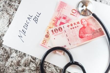 bank records: Stethoscope with wording of Medical Bill showing expensive healthcare or expensive medical bill with Macau Pataca Bank Notes Stock Photo