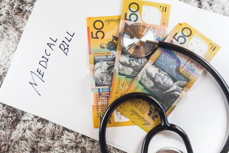 aussie: Stethoscope with wording of Medical Bill showing expensive healthcare or expensive medical bill with Australia Aussie Bank Notes Stock Photo