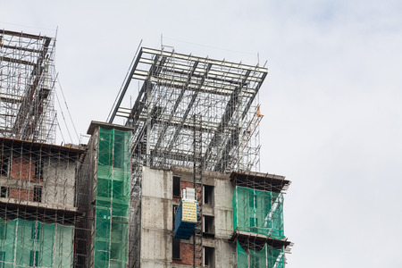 steel beam: Construction site view of crane, lift, metal beam, brick, metal ladder and concrete