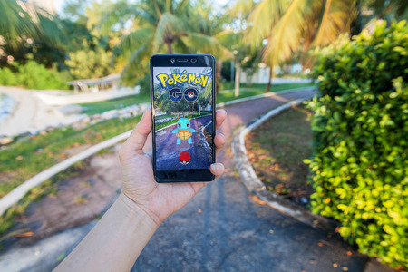 California, United States - July 2016 : Hand holding a cellphone to play Pokemon Go with blur background