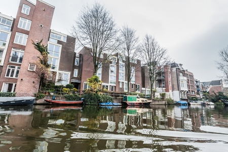 gabled houses: Amsterdam Holland, 4 December 2014 : Canal Cruises view of Amsterdam. Amsterdam is the Netherlands' capital, known for its artistic heritage, elaborate canal system and narrow houses with gabled facades, legacies of the city's 17th-century Golden Age.