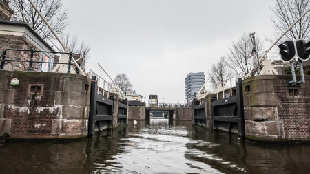 gabled: Amsterdam Holland, 4 December 2014 : Canal Cruises view of Amsterdam. Amsterdam is the Netherlands' capital, known for its artistic heritage, elaborate canal system and narrow houses with gabled facades, legacies of the city's 17th-century Golden Age. Editorial