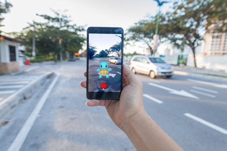 unbranded: California, United States - July 30, 2016: Close up of a man holding a unbranded smartphone while playing Pokemon Go game Editorial