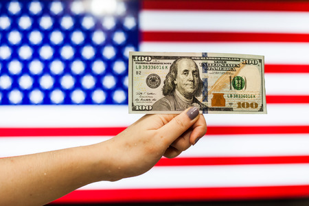 Man holding US Dollar bank note indicating market crash due to new US president with flag background Stock Photo