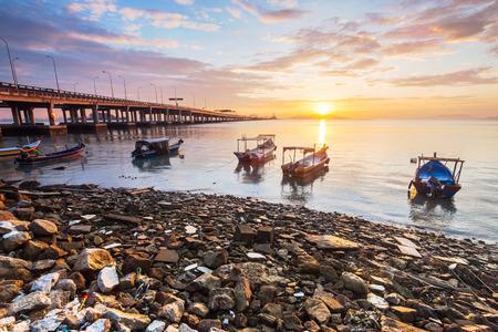 Sunrise rocky shore with fishing boat