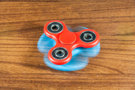 roller: Fidget Spinner in wooden isolated background for stress release during work
