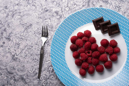 Heart of raspberry and chocolate squares on white blue dish and metal fork. Love dessert. High resolution image