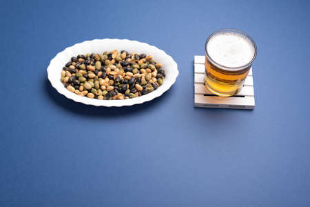 Snack and beer on white small white pallet coaster flat lay knolling of edamame and soy on dark blue desk