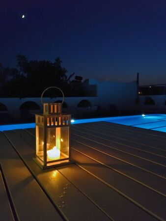 Glowing candlelight in modern lantern by the pool and moonlight with romantic atmosphere Фото со стока