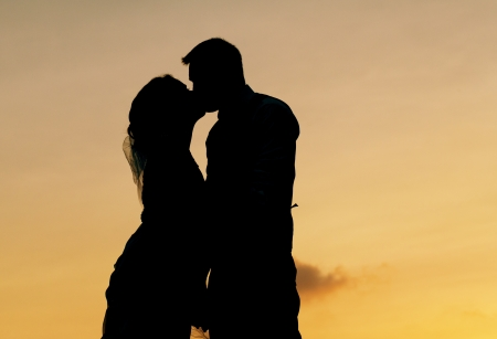 bride and groom silhouette kissing   photo