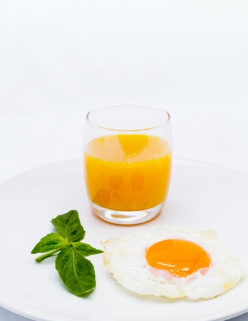 Breakfast consisting of orange juice and fried egg  photo