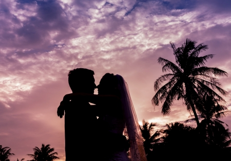 Romantic silhouette couple standing on the beach . photo