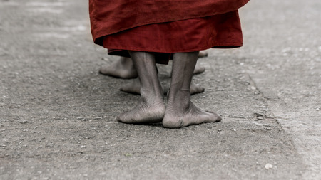 ascetic: Foots of ascetic Buddhist monk walking at the way to  Kyaikhtiyo. Stock Photo