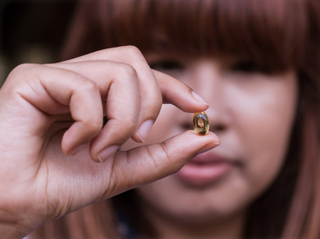 Pills of fish oil holding by young girl. Stock Photo