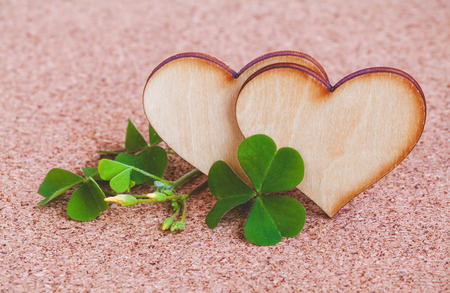 luckiness: Closeup clover leaf and stone ,wooden heart on cork background.