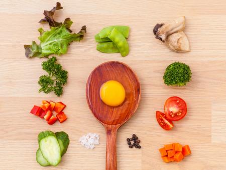 serv: Ingredients of homemade omelet on wooden panel.