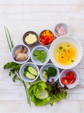 raw vegetables: Ingredients of homemade omelet on wooden panel.
