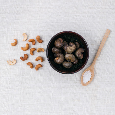 cashew tree: Raw cashews nut in the bowl with salt on white table.