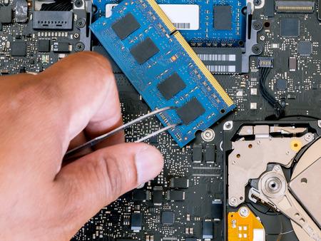 teclado de computadora: T�cnico parte actualizaci�n de soporte y fijaci�n de port�til. Foto de archivo