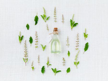 聖なるバジルの葉と花のエッセンシャル オイルのボトル。